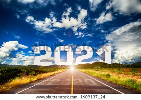 The word 2021 behind the mountain of empty asphalt road at golden sunset and beautiful blue sky. Concept for vision year 2021.