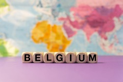 The word Belgium written with wooden dices in front of a purple background and a geographic map
