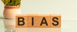The word BIAS message word on a wooden desk on cube blocks with a flower on background