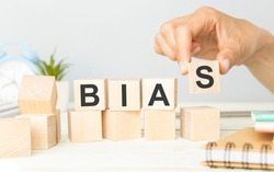 The word BIAS, spelt with wooden letter tiles over a white background.