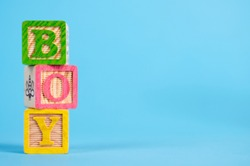 The word 'BOY' in coloured wooden blocks, with a blue background. Perfect for an original and funny baby card or an invitation for a babyshower. Including copy space for your own text.
