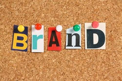 The word Brand in cut out magazine letters pinned to a cork notice board. An essential part of any Business Plan to generate sales and attract customers is the establishment of a brand.
