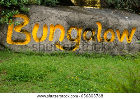 "The word ""Bungalow"" inscribed on a rock #656803768"