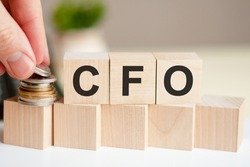 The word CFO written on wood cubes. A man's hand places the coins on the surface of the cube. Business and finance concept. CFO short for Chief Financial Officer