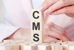 The word CMS on a wooden toy blocks with womans hands, pink background. Business concept. CMS - short for content management system