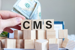 the word CMS on the wooden blocks and a money in the background, business concept. CMS - short for Content Management System.