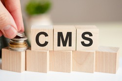 The word CMS written on wood cubes. A man's hand places the coins on the surface of the cube. Green plant in a flower pot on the background.  CMS short for Content Management System