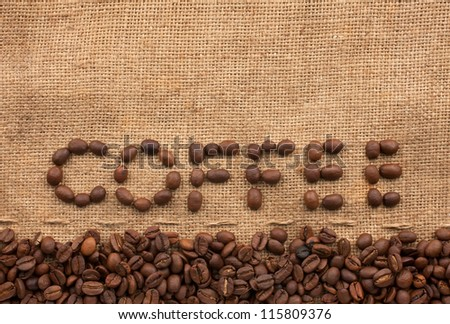 The word coffee made from coffee beans on sackcloth next to coffee beans