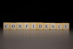 The word CONFIDENCE written on wooden cubes isolated on a black background...