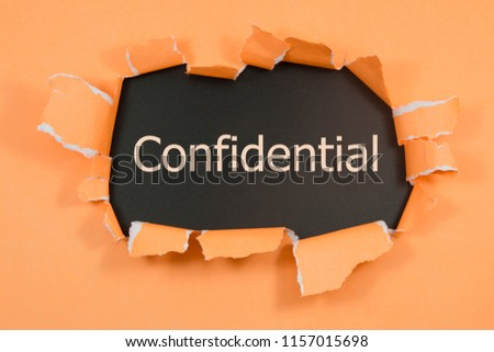 The word confidential appearing behind torn paper.