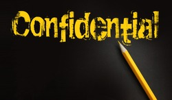 The word confidential yellow on black and a pencil besides. Secret personal or business data concept.