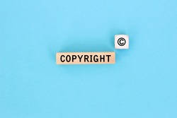 The word copyright and copyright symbol on wooden blocks on Blue background. Concept of patenting or copyright protection.