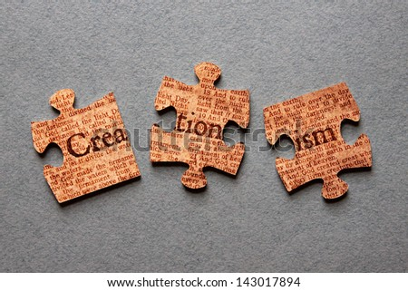 The word Creationism against background of Genesis text printed on mismatched jigsaw pieces.
