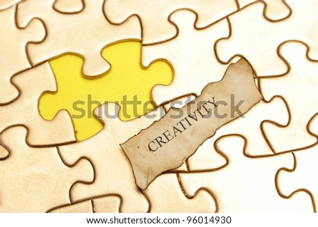 The word creative rests on a gold puzzle with a blank piece marked in yellow.