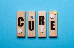 The word cure written on wooden blocks on a blue background with multi-colored pills