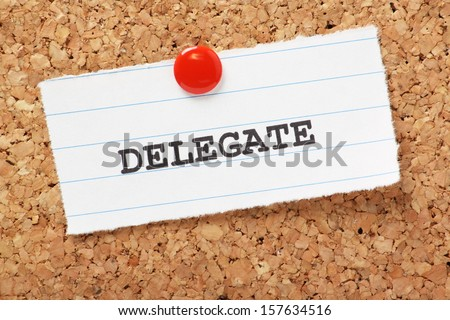 The word Delegate typed onto a scrap of lined paper and pinned to a cork notice board. Knowing when to delegate to others is an essential skill in leadership and time management.