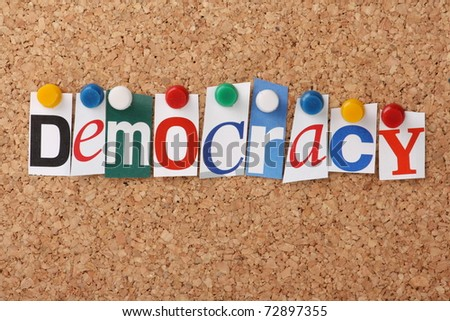 The word Democracy in cut out magazine letters pinned to a cork notice board