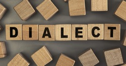 The word DIALECT on small wooden blocks at the desk. Conceptual photo. Top view