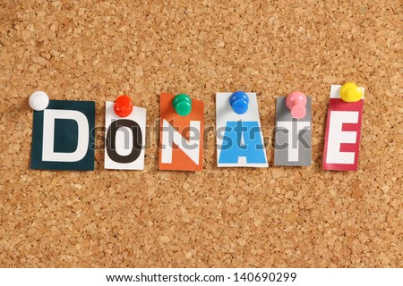 The word Donate in cut out magazine letters pinned to a cork notice board