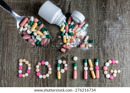 The word doping written with pills on a wooden background.