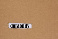 The word durability is written in a hole in the cardboard.