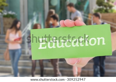 The word education and hand showing card against happy students walking and chatting outside