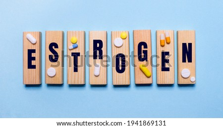 The word ESTROGEN is written on wooden blocks on a light blue table near the pills. Medical concept Foto stock ©