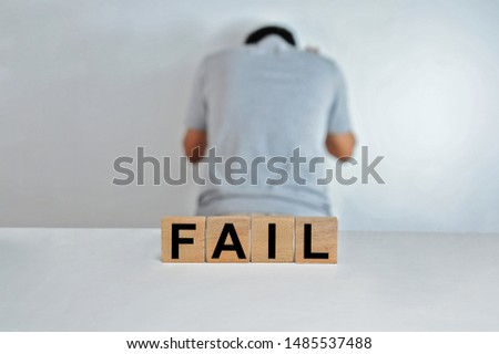 The word fail on wooden cubes, a person doing fail gesture on blur background, light wooden cubes signs, symbols signs. Business office, site content #1485537488