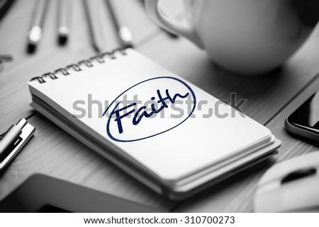 The word faith against notepad on desk