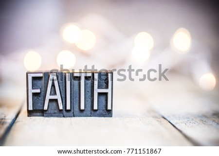 The word FAITH written in vintage metal letterpress type on a bokeh light and wooden background. #771151867