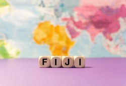 The word Fiji written with wooden dices in front of a purple background and a geographic map