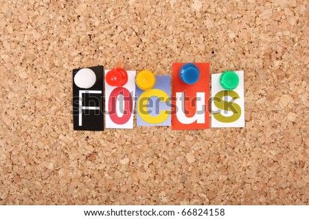 The word Focus in cut out magazine letters pinned to a cork notice board