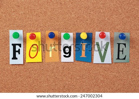 The word Forgive in cut out magazine letters pinned to a cork board.