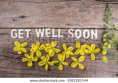 The word 'GET WELL SOON' with spring flowers on wooden background. #1082285144