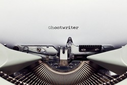 The word ghostwriter typed on the paper with a vintage typewriter. Close up flat lay view