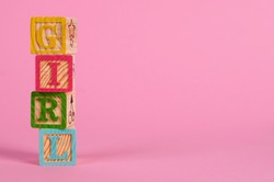The word 'GIRL' in coloured wooden blocks, with a pink background. Perfect for an original and funny baby card or an invitation for a babyshower. Including copy space for your own text.