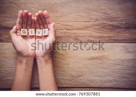 "The word ""GIVE"" in hands in cupped shape. Concepts of sharing, giving,"