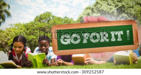 The word go for it! and hand showing chalkboard against children lying on grass and reading books