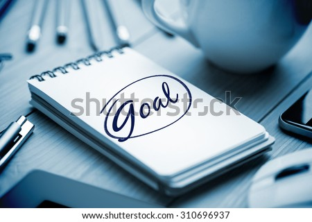 The word goal against notepad on desk