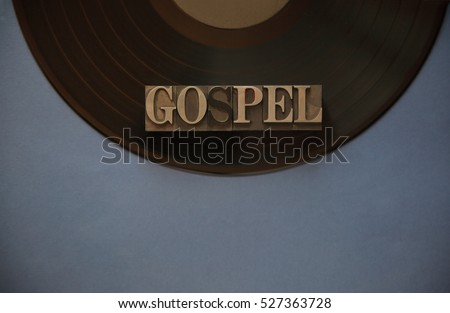 The word gospel in old metal type on a black vinyl record with a blue-gray background for text #527363728
