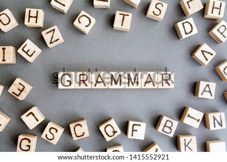 the word grammar wooden cubes with burnt letters, study of grammar of different languages,  gray background top view, scattered cubes around random letters Stock photo ©