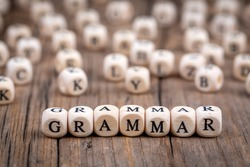 The word grammar wooden cubes with burnt letters, study of grammar of different languages, wooden background top view, scattered cubes around random letters