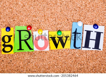 The word growth in cut out magazine letters pinned to a cork notice board
