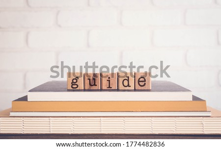 The word GUIDE, alphabets on wooden rubber stamps on top of books with bricks background, blank copy space, vintage minimal style. Concepts of instruction, learning, manual, policy, and education. ストックフォト ©