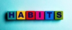 The word HABITS is written on multicolored bright wooden cubes on a light blue background