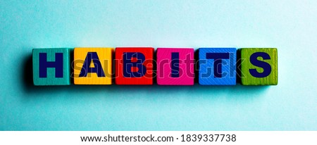 The word HABITS is written on multicolored bright wooden cubes on a light blue background Stock photo ©