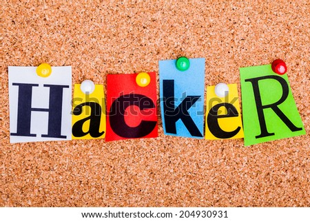 The word Hacker in cut out magazine letters pinned to a cork notice board