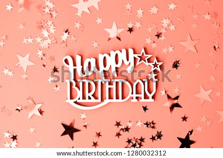 The word happy birthday on a background of coral color with stars.