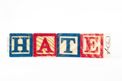 the word HATE formed from cubical wooden letter box.