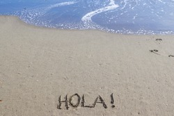 The word hello in Spanish with an exclamation point (Hola!) on a golden sandy beach with blue ocean waves rolling in from above.  Peaceful, tranquil, tropical, vacation concepts.
